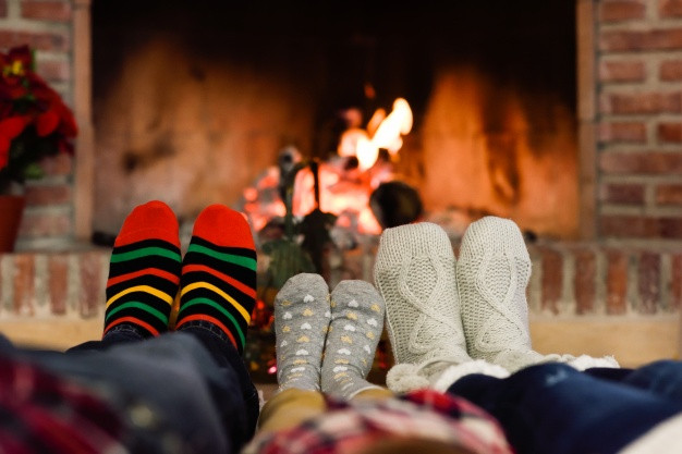 Christmas Sock Fireplace  Feet in christmas socks near fireplace relaxing at home